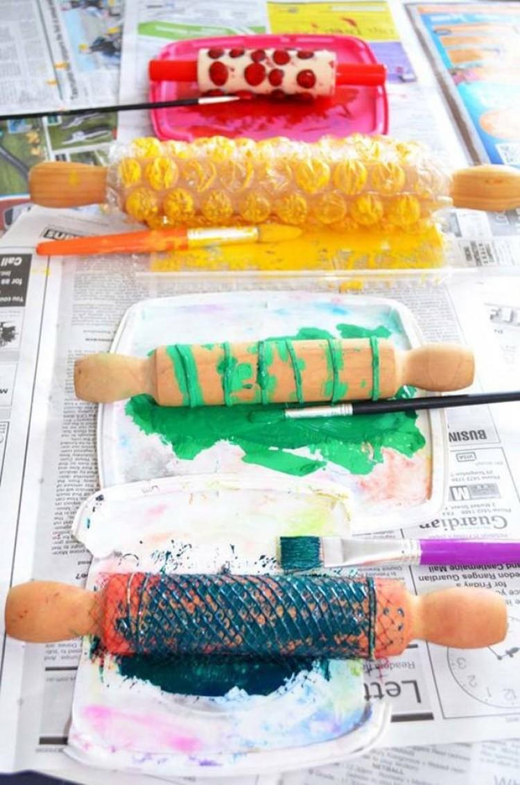Owiń różne materiały wokół wałka do ciasta izanurz go w farbie. Rzuć go na zwykłym papierze do kolorowych wzorów.